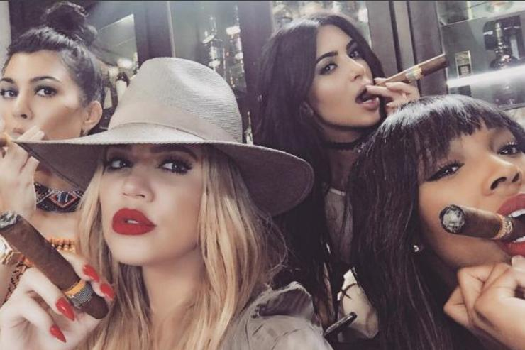 The Kardashian sisters and a friend do a group selfie with cigars.